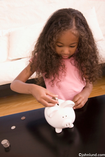 Cute young black girl putting her money into a piggy bank learning to save at an early age, and to plan for the future.