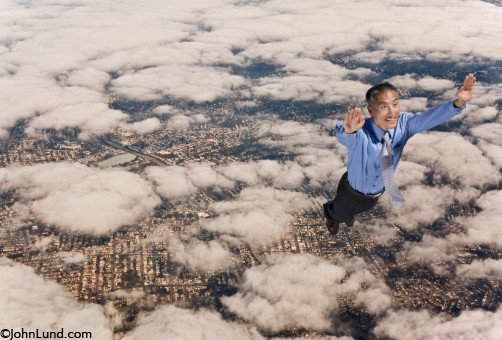 A businessman of Asian descent soars free high above the urban environment experiencing the joy of success. Great picture for advertising for small or big business. Picture of man flying through the sky.