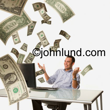 Dollars fly past a business man out of a computer in this concept image about online oppotunity, banking, Success and finance. He turned his computer into a money making machine.