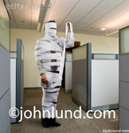 Picture of a man in an office wrapped in adding mading tape and holding the end up in front of his face to examine the numbers.
