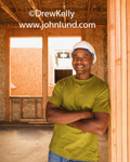 Happy black male construction worker smiling and leaning against an unfinished doorway in a building under construction.  The man is wearing a green t shirt and a white hard hat.  Pictures of hard working black men.