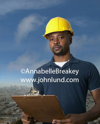 Inspirational photo of a black small businessman, a contractor, wearing a yellow hard hat and holding a clipboard. The man is looking at the camera with an air of confidence. Small business black contractor pictures for advertising.