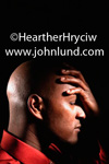 Close up photo of a black man holding his hand against his forehead like maybe he has a headache or just realized there is a big problem with something.  Photo of a bald black man with a headache.  Unhappy African american man .