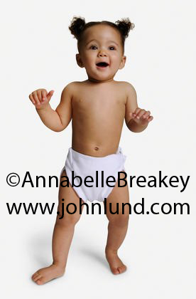 Picture of  an african american baby in diapers standing up on her own.  The baby is on a white background.  Hair in cute little pigtails. Black baby pics.