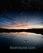 This stunning water conservation image shows a single drop of water falling into the still waters of a lake at sunset with the twilight sky merging into a carpet stars, an image of mystery, wonder, consequences and environmental issues.