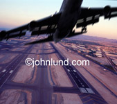 Lifestyle stock photo of a plane taking off over an airport. Dramatic take-off photo of a jet airliner with the camera angle under the plane but high above the ground.