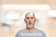 In this photo a senior man in a vaguely medical or retirement home setting has been transformed into a jigsaw puzzle with a portion of his head missing as shown by a missing piece of the puzzle.