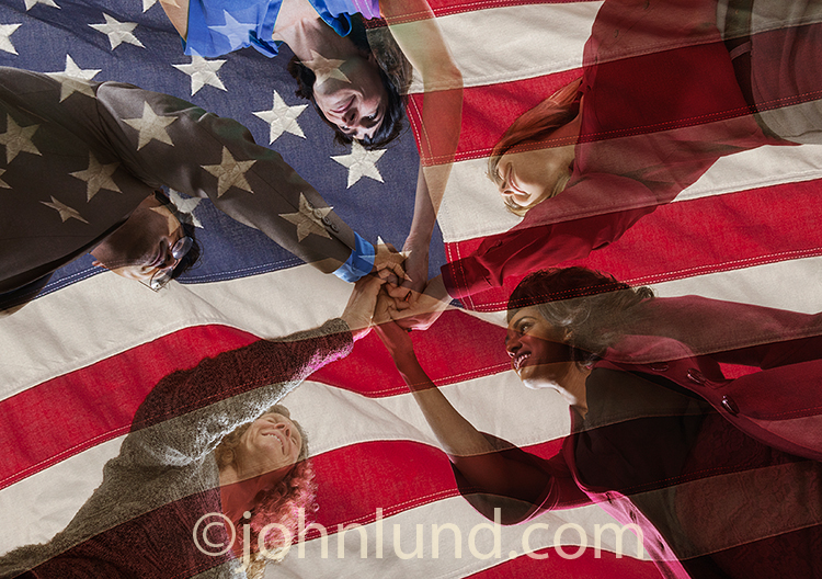 American diversity and teamwork is shown in this stock photo of five people joining hands superimposed against an American Flag.