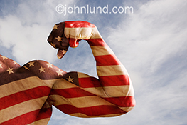 A strong America is vividly illustrated in this stock photo of a powerful bicept double exposed with the American flag against a lightly clouded blue sky.