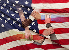 A diverse group of hands come together in teamwork superimposed over the American Flag in this stock photo about America, teamwork, and the strength of diversity.