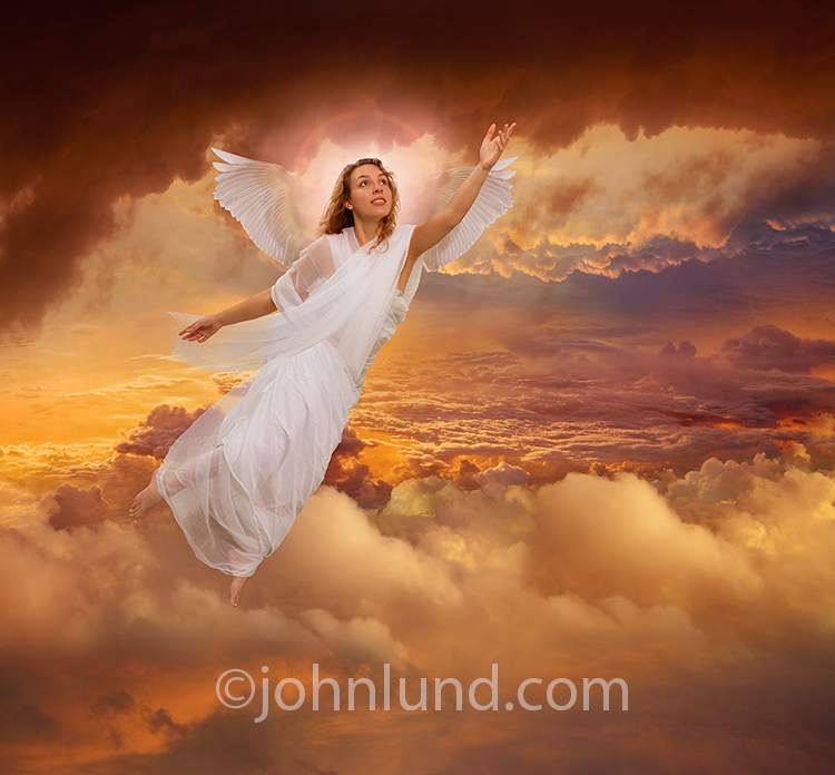 A beautiful angel with white feathered wings and a glowing halo, wearing a white flowing gown, rises up through a birlliant sunset cloudscape as she ascends to heaven.