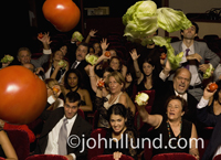 An angry audience throws vegetables towards a speaker in this humorous concept stock photo about presentation pitfalls.