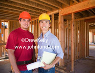 Mulit-ethnic men, an hispanic and an asian, are posing for the camera on the jobsite.  One is wearing an orange hard had and the other a yellow hard hat.  Advertising pictures for contracters, builders, remodlers and other uses.