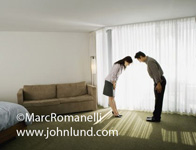 An Asian couple in a motel room are bowing to each other as a sign of respect. A man and a woman bowing to each other after a business meeting.