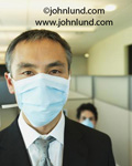 Asians wearing breathing masks. This asian man, a businessman, is wearing a surgical mask as is a woman in the background.  Close up picture of man in mask. Wearing surgical masks in the office.