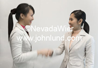 Asian business women shaking hands over a business deal. The business women shaking hands are smiling and happy. Both have long ponytails. Teamwork and Handshake photo.