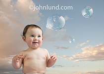 A baby in diapers stares with delight at bubbles floating down around her as she sits outdoors on a warm afternoon.