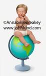 Funny picture of a baby in diapers sitting on top of a world globe. The baby has a hillarious expresion on his face. Blond baby boy in diapers. Blond baby pic.