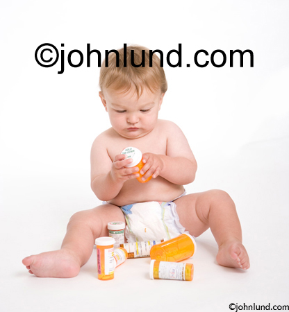 Small baby wearing diapers playing with prescription drugs and struggling to open prescription medicine bottles. Picture of childproof pill bottle. Picture of toddler with perscription pill bottles.