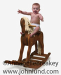 Happy baby riding a wooden rocking horse. Baby is wearing a diaper and has his hands out to his sides.  Fun baby picture.