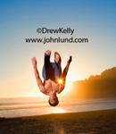 Image of a happy man  joyfully doing a backflip at the beach as the sun sets behind him. Mans head is pointed at the ground with arms at his sides and feet above him.