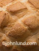 In this close up overhead shot of baked French bread one can almost taste the goodness and imagine tearing out a big chunk and the chewiness of the crust.