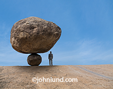 This image of a businessman standing beneath a huge boulder balancing on a smaller rock is a humorous metaphor for business risk, danger and adversity.