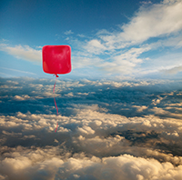 A square, red balloon floats high in the sky above the clouds, a different kind of balloon than the ordinary rounded ones.
