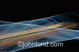 Big data, bandwidth, communications technology, and networking are all illustrated in this stock photo featuring an intricate and complex tunnel of blue light streaks filled with speeding lights of red, orange, yellow green and blue, light indicative of s