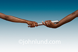 A baton is passed from one woman's hand to another in a stock photo about teamwork, success and women's issues.