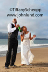 A bride and groom are on the beach celebrating with wedding by openning a bottle of champagne. The groom has just popped the cork and champagne is spraying into the air. Happy newlyweds with champagne on the beach.