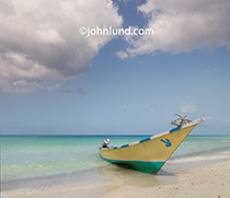 A beached fishing boat rests on a beautiful white sand beach on the Yemeni Island of Socotra.