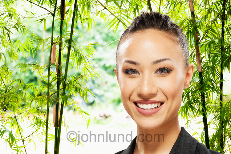 This beautiful Asian woman stock image showcases the woman against a background of dappled light seen through bamboo stalks.