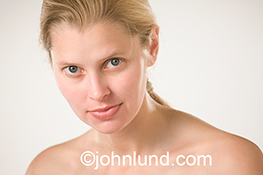 This beautiful blonde woman seen without make up and against a white background personifies purity, simplicity and natural beauty.