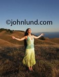Woman standing on a hillside facing the sun with her arms out stretched head tilted up and with her eyes closed.  The beautiful Hispanic woman has long dark hair. Spiritual pics of women.