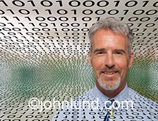 A pleased businessman stands in front of binary numbers stretching back into the distance behind him in a stock photo about connections, cloud computing, and business in the digital age.