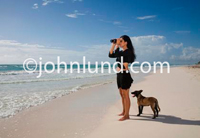 Photo of a woman standing at the edge of the lapping waves from the ocean with the beach extending out into the distance. She is looking out over the ocean with a pair of binoculars. Woman Searching. The woman's dog is with her.