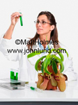 Picture of a woman scientist looking at a test tube full of a green liquid. She is wearing a white lab coat and glasses. She has long brown hair.  Bio fuel research photo.