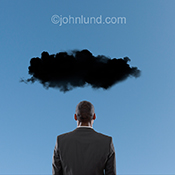 A black cloud hovers over a man's head as he looks away in contemplation.