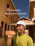 Picture of a hard working black construction worker carrying a wooden beam on his shoulder. The man has a green shirt and white hard hat. Background is a building under construction. Men working ad pictures.