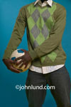 Picture of a black man in a cardigan sweater holding a soccer ball at his hip with both hands. Shoulders to knees only. Picture of an African man clutching a futbol to his side.