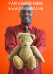 Teddy bear picture. A man is holding out a teddy bear toward the camera. African American man offering up a teddy bear for you. Cute fuzzy little teddy bear picture. Advertising photos with teddy bears.
