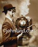Stock photo of a business man wearing blinders and oblivious to an on rushing locomotive illustrating the danger of tunnel vision and short sightedness.