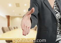 Close up of a woman executive's hand outstretched towards the camera, offering a handshake in a boardroom setting.