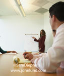 Picture of a business meeting. A woman executive is giving a presentation, pointing to a graph. Woman in maroon business suit speaking to board members.