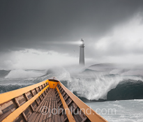 This stock image features a boat approaching a lighthouse through rough seas in an image about challenge, risk, danger and salvation be it physical or spiritual.