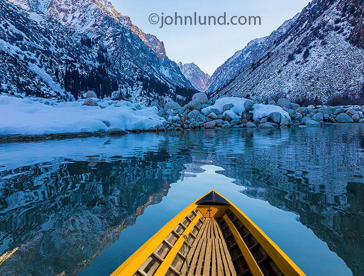Solitude and tranquility are powerfully shown in this stock photo of a bright yellow boat on a serene mountain lake.