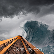 A boat cuts through huge storm waves in a stock photo about challenge, risk, danger and tenacity.