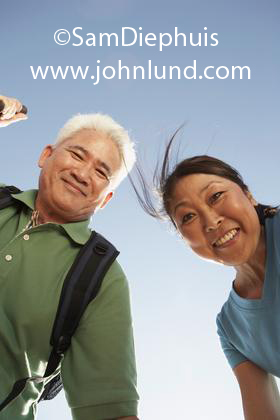A mature couple of Asian descent, Japanese or Chinese, looking down and directly at the camera.  The couple is smiling and are set against a clear blue cloudless sky. He has gray hair and a green shirt and he is wearing a backpack.