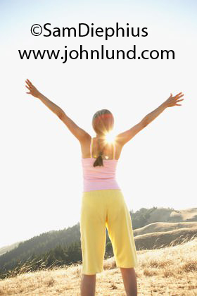 Stock photo of a senior woman, a boomer, stretching on a hillside with the sun directly in front of her showing over her shoulder.